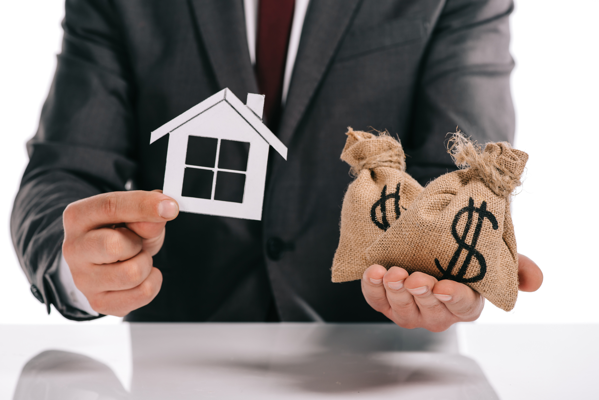 Cropped view of mortgage broker holding paper house and moneybags isolated on white