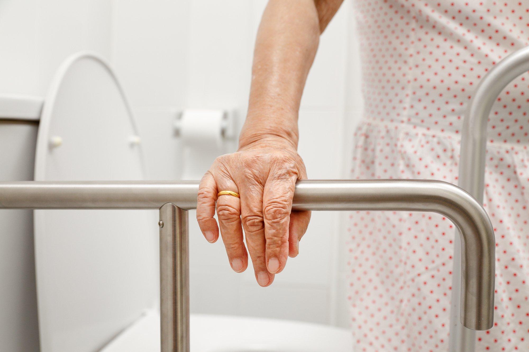 Elderly woman holding on handrail in toilet