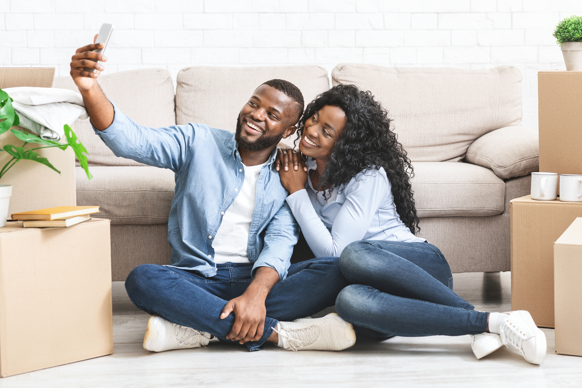 Happy couple moving in new apartment, taking selfie on phone