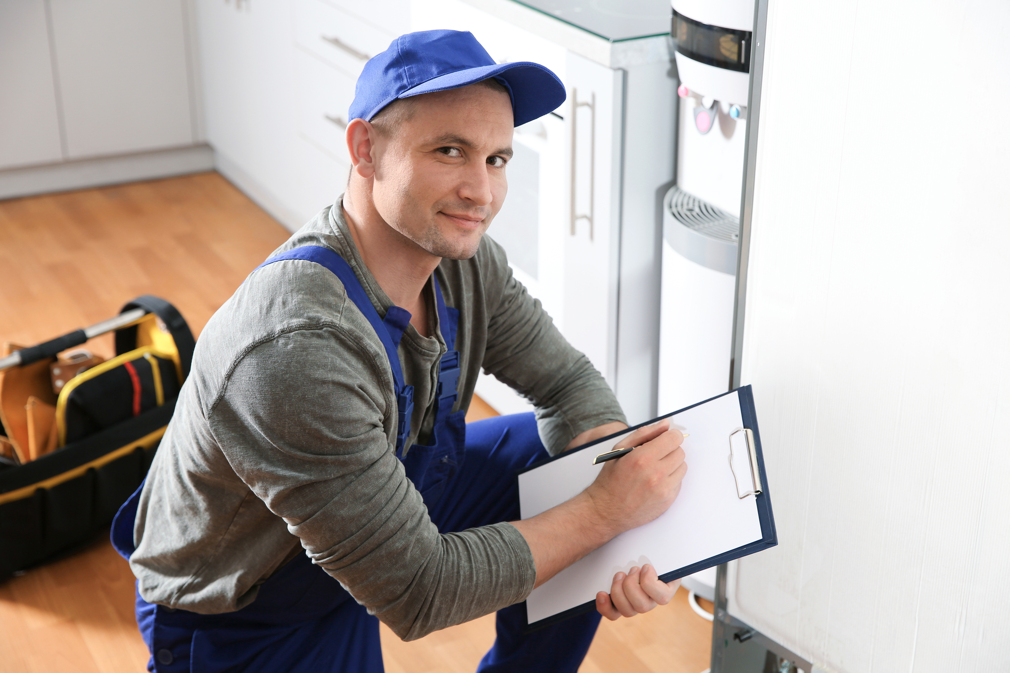 Male technician with clipboard examining broken refrigerator in kitchen