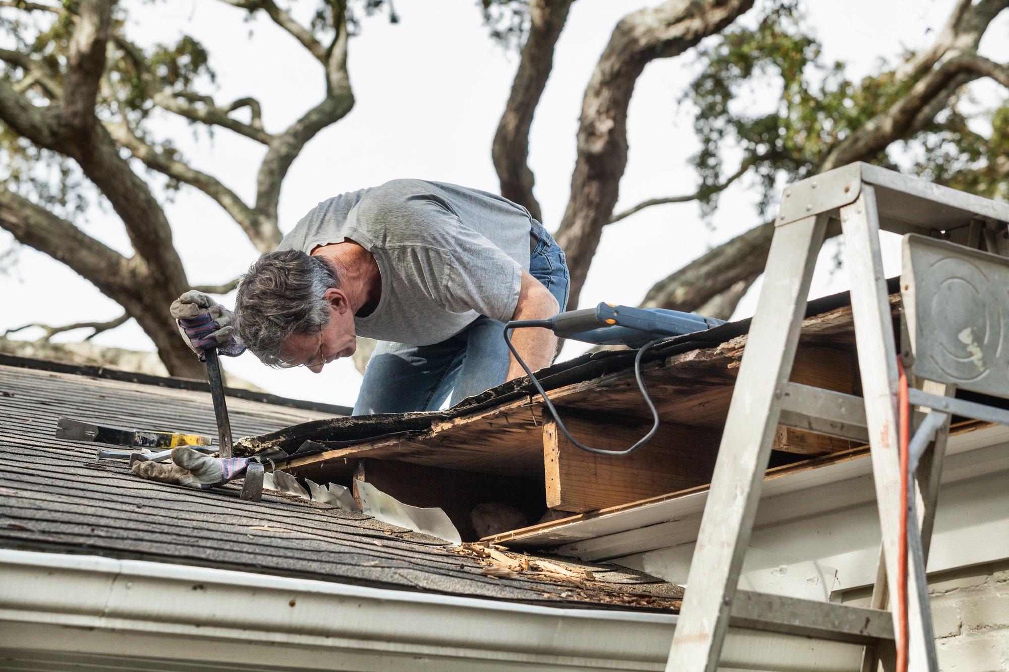 Man Examining and Repairing Leaking House Roof