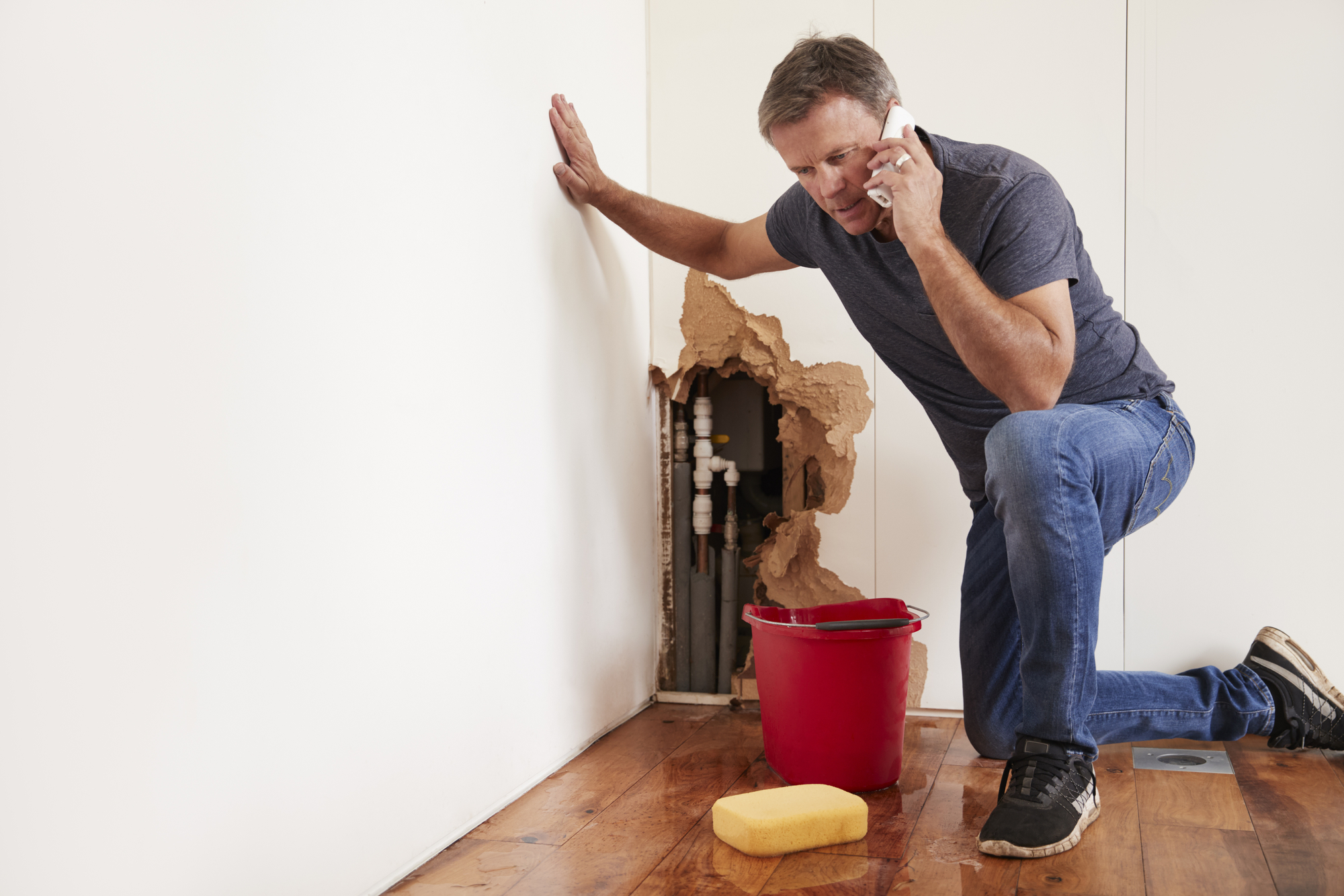 Middle aged man with a burst water pipe
